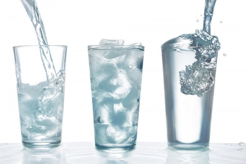 Drinking water being poured into glass with ice cubes