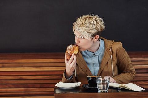 Young woman with trendy blonde hair looking away while taking a bite from her pastry, at a table in a modern cafe with a dark grey wall